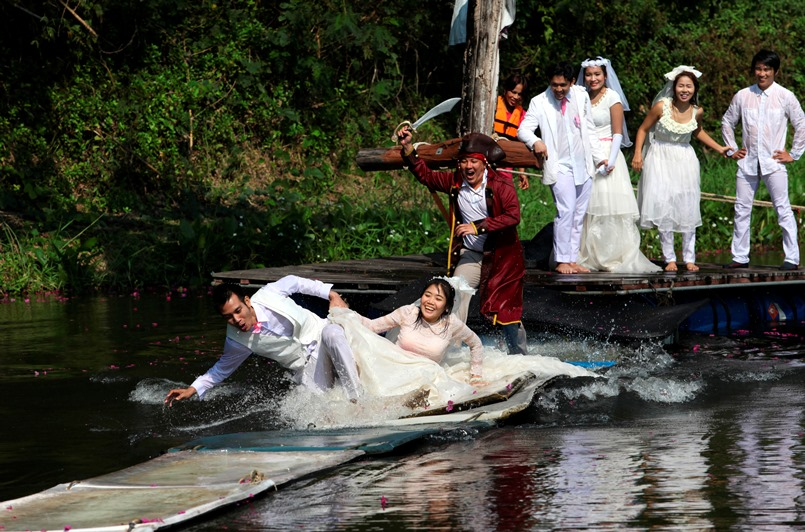 Thai groom and bride, Sorawich Changtor (front L), 28, and Rungnapa Panla (front R), 30, run to escape a man dressed as a pirate as (behind L-R) Prasit Rangsiyawong, 29, Varuttaon Rangsiyawong, 27, Chutima Imsuntear, 37, and Sopon Sapaotong, 41, look on during a wedding ceremony ahead of Valentine's Day in Prachin Buri province, east of Bangkok February 13, 2013. Three Thai couples took part in the wedding ceremony arranged by a Thai resort that aimed to strengthen the relationships of the couples by doing fun activities.  REUTERS/Kerek Wongsa    (THAILAND - Tags: SOCIETY) - RTR3DQ1T
